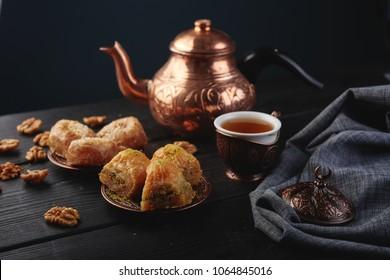 Turkish traditional Dessert Baklava with tea on dark background. Fresh and healthy dessert.