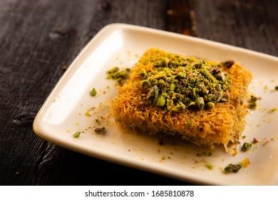 Turkish traditional dessert kadayif on a wood table