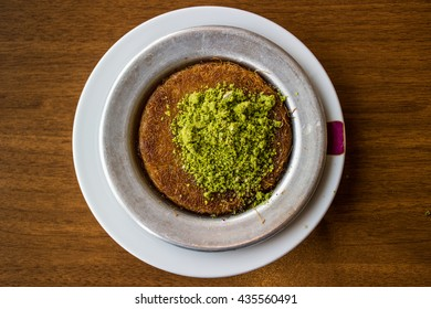 Turkish traditional dessert kunefe with pistachio powder at the restaurant top view