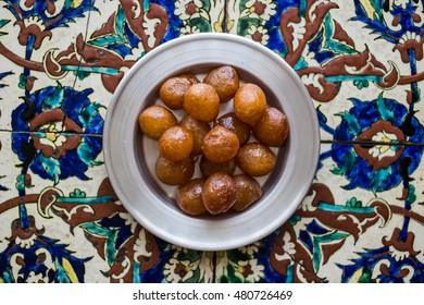 Turkish Traditional Dessert Lokma on a Ottoman Pattern Surface.