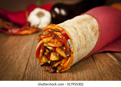 Turkish traditional doner with vegetables cheddar cheese wrap on wooden background