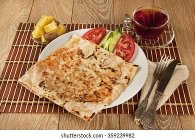 Turkish traditional Gozleme pita potatoes with black tea