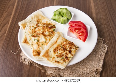 Turkish traditional Gozleme pita potatoes with cucumber and sliced tomato