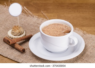 Turkish Traditional Hot Drink Sahlep with cinnamon sticks on burlap background