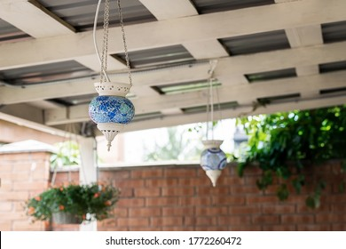 Turkish traditional oriental blue mosaic galss lantern lamp hanged on wooden roof of pergola patio canopy at backyard outdoor. Home decoration design.