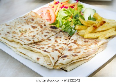 Turkish Traditional Ramadan Food Bread Gozleme serving with french fries, tomato and arugula on white plate