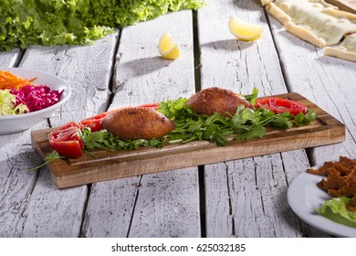Turkish Traditional Ramadan Food icli kofte ( meatball ) falafel on parsley with tomato slice on wood background.