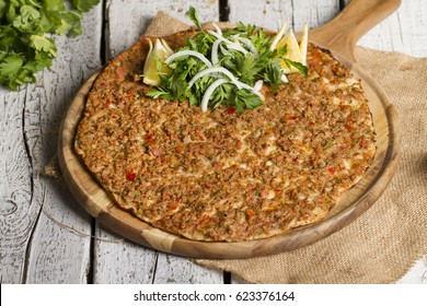 Turkish Traditional Ramadan Food Lahmacun on white rustic wooden background with salad.
