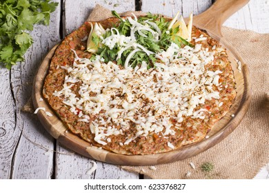 Turkish Traditional Ramadan Food Lahmacun with kasar cheese on top. Isolated on white rustic wooden background with salad.