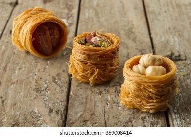 Turkish traditional ramadan pastry dessert kunafa (traditoin east sweets) on wooden background