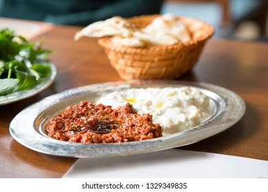 Turkish traditional snack Antep Ezme and Aubergine Yogurt Paste on wood table with herbs and lavash bread.