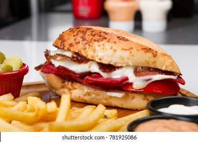 Turkish Traditional Snack Sandwich famous in Izmir which is Cesme Kumru ingredients with sliced sausage, ham, lettuce, tomato, cheddar cheese, melting kasar and pickles isolated on white background.
