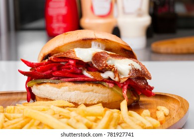 Turkish Traditional Snack Sandwich is Mix Cheeseburger ingredients with sliced sausage, ham, lettuce, tomato, cheddar cheese, melting kasar, french fries and pickles isolated on white background.