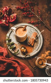 Turkish traditional wintertime hot drink Salep. Mug of sweet warming Salep drink with ground cinnamon over rusty table background with pomegranate. Turkish seasonal cuisine, Christmas, New Year mood
