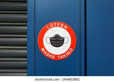 "Turkish Warning Sticker On A Close-Up Blue Door. Translation:""Please Wear Mask"""