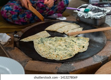 Turkish woman prepares Gozleme - traditional dish in the form of flatbread stuffed with greens and cheese, wrapped inside. Baked in a pan called a saj. Selective focus