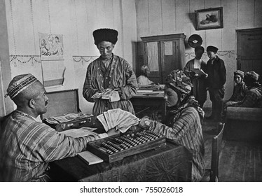 Turkmenian collective farmers receiving their share of yearly profits in the 1930s. The farm administrator calculates with an Abacus. Pictures of Stalin and Lenin hang on the walls.