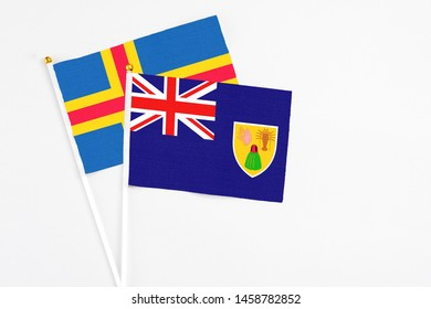 Turks And Caicos Islands and Aland Islands stick flags on white background. High quality fabric, miniature national flag. Peaceful global concept.White floor for copy space.
