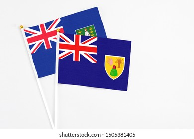 Turks And Caicos Islands and British Virgin Islands stick flags on white background. High quality fabric, miniature national flag. Peaceful global concept.White floor for copy space.