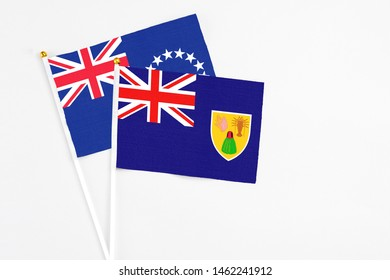 Turks And Caicos Islands and Cook Islands stick flags on white background. High quality fabric, miniature national flag. Peaceful global concept.White floor for copy space.