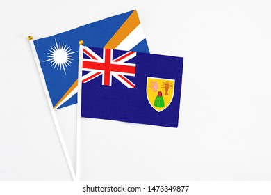 Turks And Caicos Islands and Marshall Islands stick flags on white background. High quality fabric, miniature national flag. Peaceful global concept.White floor for copy space.