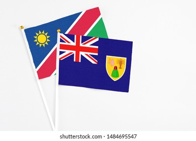 Turks And Caicos Islands and Namibia stick flags on white background. High quality fabric, miniature national flag. Peaceful global concept.White floor for copy space.