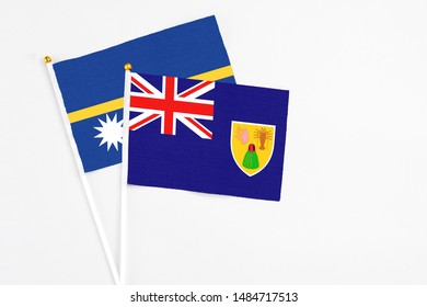 Turks And Caicos Islands and Nauru stick flags on white background. High quality fabric, miniature national flag. Peaceful global concept.White floor for copy space.