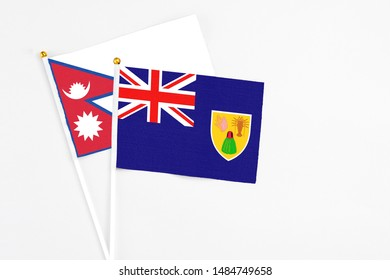 Turks And Caicos Islands and Nepal stick flags on white background. High quality fabric, miniature national flag. Peaceful global concept.White floor for copy space.