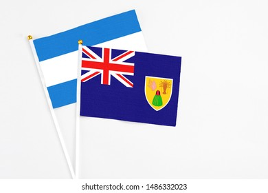 Turks And Caicos Islands and Nicaragua stick flags on white background. High quality fabric, miniature national flag. Peaceful global concept.White floor for copy space.