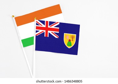 Turks And Caicos Islands and Niger stick flags on white background. High quality fabric, miniature national flag. Peaceful global concept.White floor for copy space.