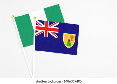 Turks And Caicos Islands and Nigeria stick flags on white background. High quality fabric, miniature national flag. Peaceful global concept.White floor for copy space.