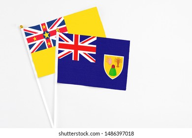Turks And Caicos Islands and Niue stick flags on white background. High quality fabric, miniature national flag. Peaceful global concept.White floor for copy space.