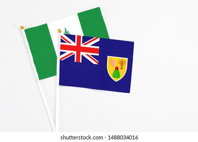 Turks And Caicos Islands and Norfolk Island stick flags on white background. High quality fabric, miniature national flag. Peaceful global concept.White floor for copy space.
