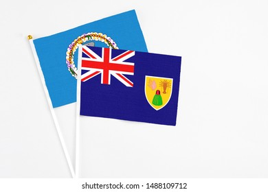 Turks And Caicos Islands and Northern Mariana Islands stick flags on white background. High quality fabric, miniature national flag. Peaceful global concept.White floor for copy space.