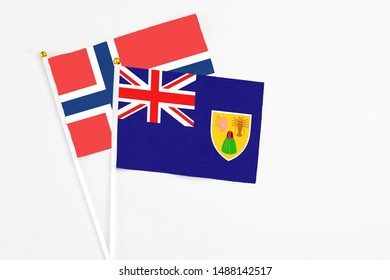 Turks And Caicos Islands and Norway stick flags on white background. High quality fabric, miniature national flag. Peaceful global concept.White floor for copy space.