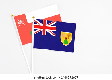 Turks And Caicos Islands and Oman stick flags on white background. High quality fabric, miniature national flag. Peaceful global concept.White floor for copy space.