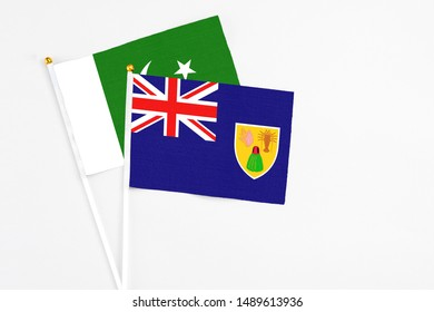 Turks And Caicos Islands and Pakistan stick flags on white background. High quality fabric, miniature national flag. Peaceful global concept.White floor for copy space.