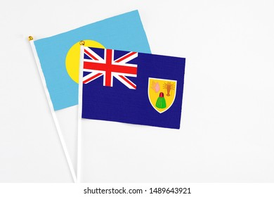 Turks And Caicos Islands and Palau stick flags on white background. High quality fabric, miniature national flag. Peaceful global concept.White floor for copy space.