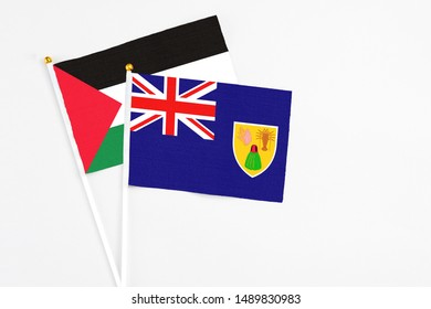 Turks And Caicos Islands and Palestine stick flags on white background. High quality fabric, miniature national flag. Peaceful global concept.White floor for copy space.