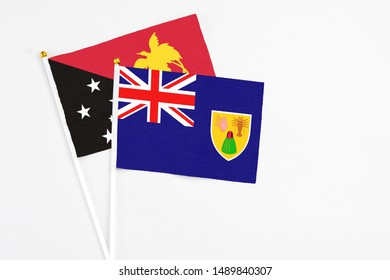 Turks And Caicos Islands and Papua New Guinea stick flags on white background. High quality fabric, miniature national flag. Peaceful global concept.White floor for copy space.