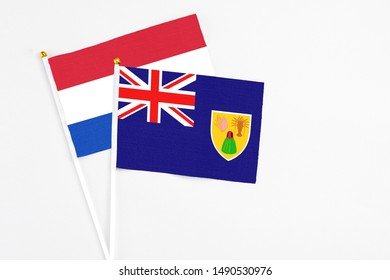 Turks And Caicos Islands and Paraguay stick flags on white background. High quality fabric, miniature national flag. Peaceful global concept.White floor for copy space.