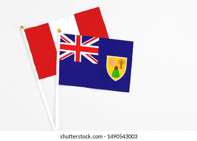 Turks And Caicos Islands and Peru stick flags on white background. High quality fabric, miniature national flag. Peaceful global concept.White floor for copy space.