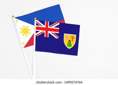 Turks And Caicos Islands and Philippines stick flags on white background. High quality fabric, miniature national flag. Peaceful global concept.White floor for copy space.