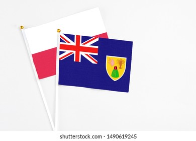 Turks And Caicos Islands and Poland stick flags on white background. High quality fabric, miniature national flag. Peaceful global concept.White floor for copy space.