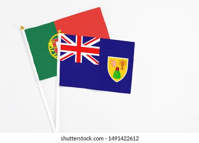 Turks And Caicos Islands and Portugal stick flags on white background. High quality fabric, miniature national flag. Peaceful global concept.White floor for copy space.
