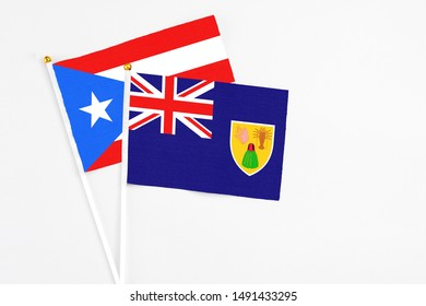 Turks And Caicos Islands and Puerto Rico stick flags on white background. High quality fabric, miniature national flag. Peaceful global concept.White floor for copy space.