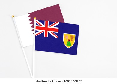Turks And Caicos Islands and Qatar stick flags on white background. High quality fabric, miniature national flag. Peaceful global concept.White floor for copy space.