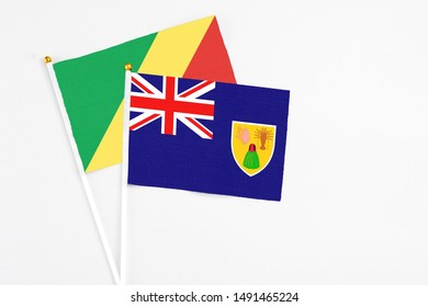 Turks And Caicos Islands and Republic Of The Congo stick flags on white background. High quality fabric, miniature national flag. Peaceful global concept.White floor for copy space.