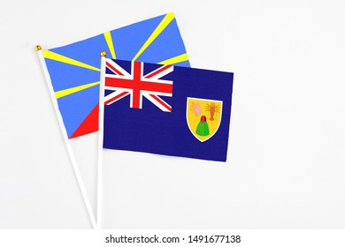 Turks And Caicos Islands and Reunion stick flags on white background. High quality fabric, miniature national flag. Peaceful global concept.White floor for copy space.