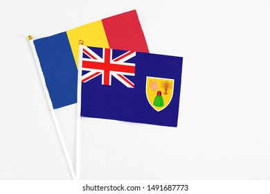 Turks And Caicos Islands and Romania stick flags on white background. High quality fabric, miniature national flag. Peaceful global concept.White floor for copy space.